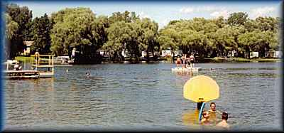 beach with diving board raft ~ Lake Lenwood Beach & Campground West Bend Wisconsin camping RV park